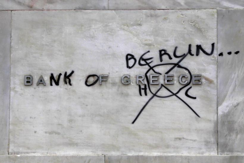 A 'Bank of Greece' sign, outside the institution, defiled by protesters Friday