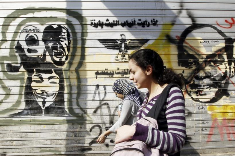 People walk in front of a wall sprayed with graffiti depicting Field Marshal Hussein Tantawi (L) and martyrs at Mohamed Mahmoud street, which leads to the Interior Ministry, where clashes between protesters and security forces took place during the revolu