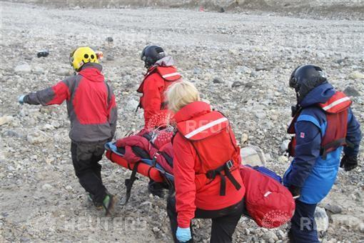 Rescuers carry one of the four youths injured in a polar bear attack on Spitsbergen
