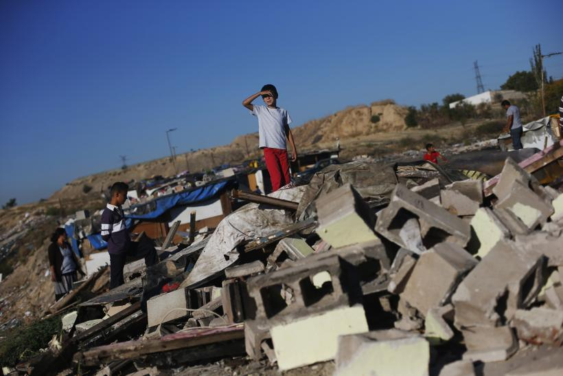 "A child looks on at the remains of a home demolished by police during an operation in Madrid's ""El Gallinero"" slum."