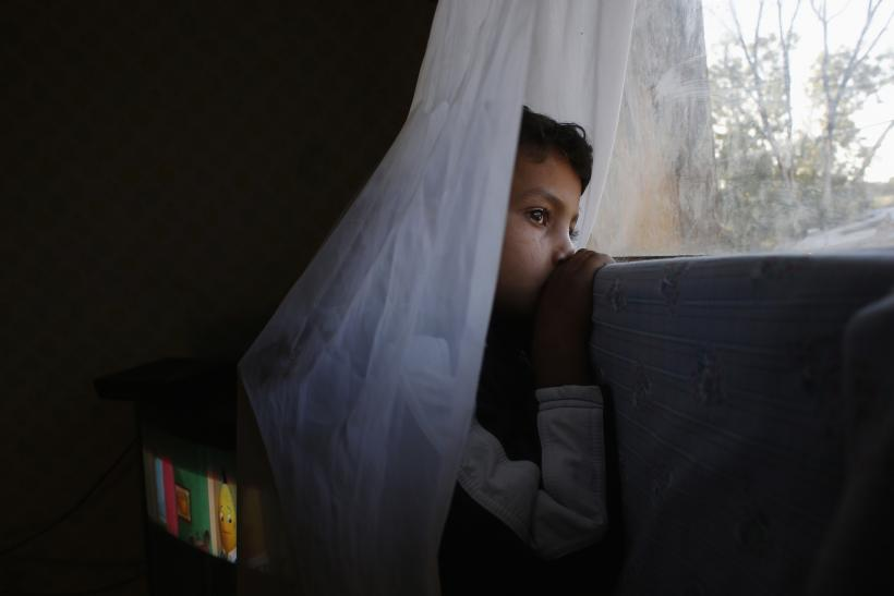 "Six-year-old Abel watches from his window as an excavator demolishes a neighbor's shack in Madrid's ""El Gallinero"" slum."