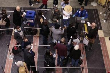 Travelers wait in line to go through TSA screening in the Ronald Reagan Washington National Airport in Arlington, Virginia