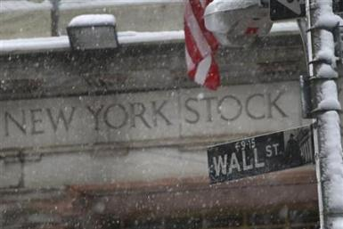 Snow falls on a Wall St. street sign in front of the New York Stock Exchange