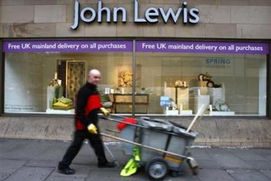 A road cleaner walks past a John Lewis store in Edinburgh, Scotland
