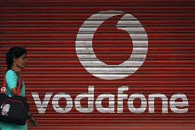 A woman walks past a large logo of Vodafone displayed on a shop in Mumbai May 20, 2010