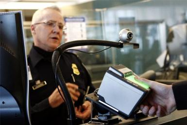 A traveler has his fingerprints scanned at the international travel entry point at JFK International Airport in New York