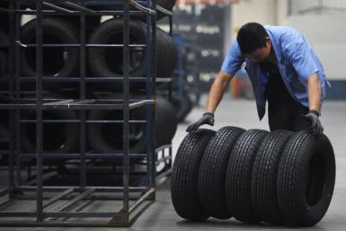 An employee moves tires at a tire factory