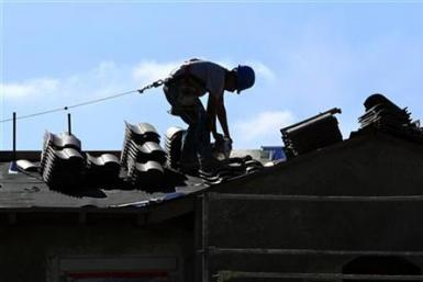 A construction worker cuts tiles as he installs a roof on a home in a new subdivision being built in San Marcos, California