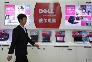 An employee walks past Dell laptops, which are displayed for sale, at a Dell outlet in Beijing