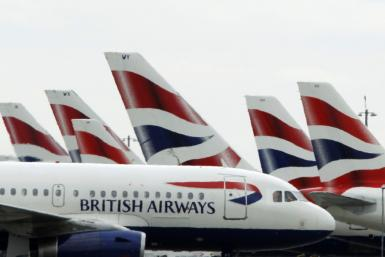 A British Airways passenger jet taxis past parked BA jets at Heathrow airport in London