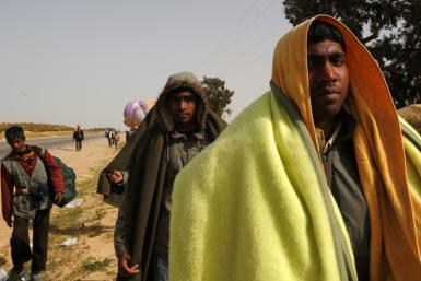 Bangladeshi evacuees walk away from the border after fleeing unrest in Libya