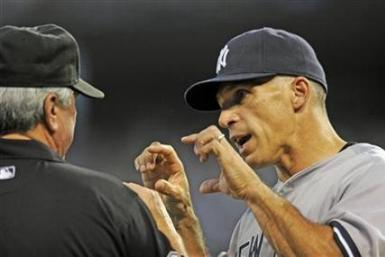 New York Yankees manager Joe Girardi (R) pleads his case with second base umpire Dana DeMuth as he challenges a solo home run by Kansas City Royals designated hitter Billy Butler that hit the railing and bounced back onto the field in the third inning dur