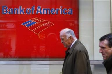 Pedestrians walk past a Bank of America sign on the street in New York