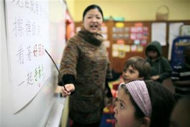 Teacher Kennis Wong points to Chinese characters on the board at Broadway Elementary School in Venice, Los Angeles
