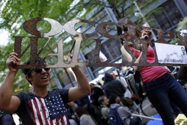 "A couple holds a welded iron ""Occupy Wall Street"" sign as they demonstrate in New York City"
