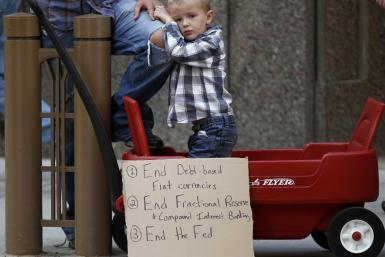 Lincoln Hallgren joins his father during a demonstration in support of the New York Occupy Wall Street protests in front of the Chicago Board of Trade Building in the financial district of Chicago