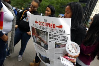A woman reads a copy of a newspaper published by the Occupy Wall Street protesters as she visits Zuccotti Park in lower Manhattan in New York
