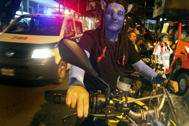 "A man dressed as a character from the movie Avatar takes part in the ""Moto Halloween Party 2010"" in Cali"