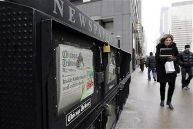 People walk past a newspaper box across from the Chicago Tribune tower in Chicago, Illinois December 8, 2008.