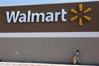 People walk past a Wal-Mart sign in Rogers, Arkansas