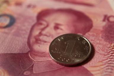 A Chinese one yuan coin and a 100 yuan banknote are seen in this picture illustration taken in Beijing