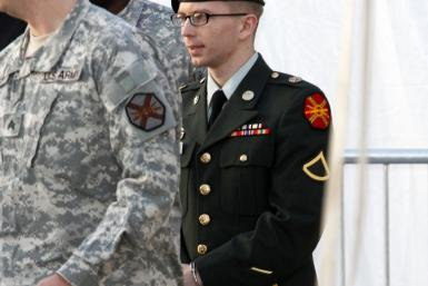 Army Pfc. Bradley Manning, in handcuffs, is escorted out of a courthouse in Fort Meade, Maryland