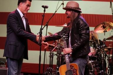 Republican presidential candidate Mitt Romney shakes hands with musician Kid Rock after Rock performed at a campaign stop for Romney's supporters in Royal Oak
