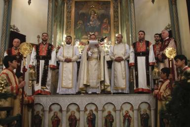 Christian clerics pray during a mass to celebrate the Orthodox Christmas at Saint Serkis church in Damascus