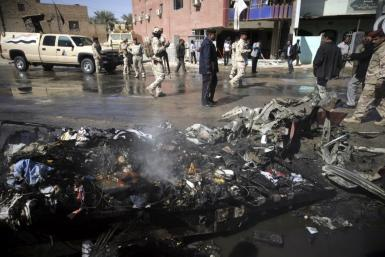 Iraqi security forces inspect the site of a bomb attack in Kerbala
