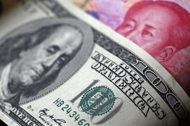 File photo of a Chinese 100 yuan banknote being placed under a $100 banknote in this photo illustration taken in Beijing