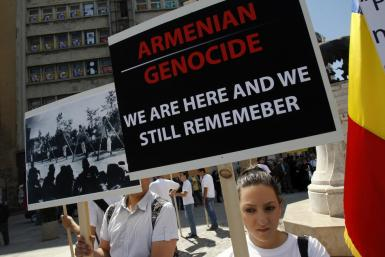 Members of Armenian community in Romania hold banners during a rally marking the anniversary of mass killings of Armenians in Ottoman Empire in 1915, in downtown Bucharest