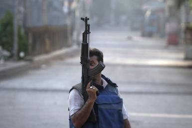 A plainclothes policeman holds a weapon as he walks down the streets during a firefight with gang members in Karachi.