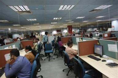 Employees work on the floor of the outsourcing company WNS in Mumbai March 19, 2012.
