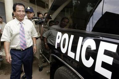 Cambodian radio station director Mam Sonando (front on L) walks towards a police vehicle after being questioned at Phnom Penh Municipality Court, in this file picture taken October 11, 2005. A Cambodian court jailed Sonando, a 71-year-old radio broadcaste