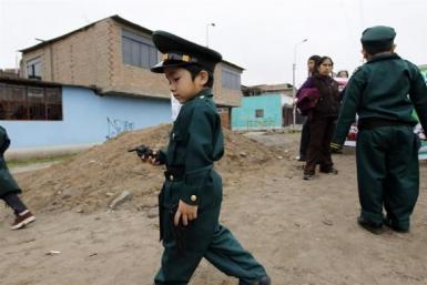 A boy dressed as a police officer plays with a toy gun