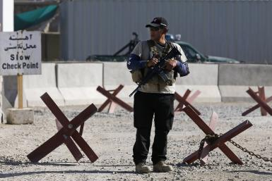A foreign security contractor from a security company keeps watch at the site of a blast, outside the counter-narcotics office near the Kabul International Airport July 22, 2014