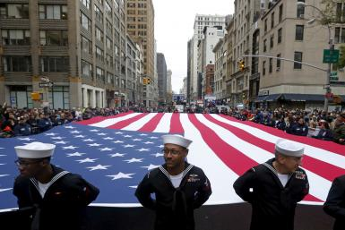 U.S. Navy personnel stand ahead of a U.S. flag during a Veteran's Day parade.