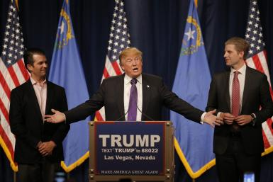 Donald Trump gestures to his sons Donald Trump Jr. (L) and Eric Trump (R)