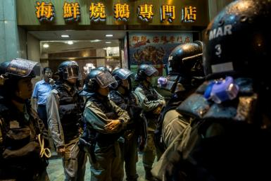 Hong Kong riot police stand in front of a restaurant while patrolling after an anti-government rally which, for the first time in weeks, saw no major confronations with officers
