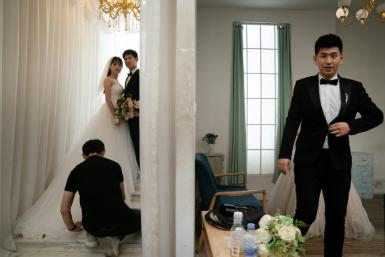 An army of helpers take photographs and manage sets, adjust clothing and add accessories at the Love Story in Rome Studio in Beijing