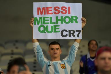"A fan of Argentina displays a placard reading ""Messi better than CR7"" at the start of the Copa America match against Paraguay in June"