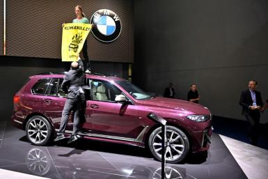 A Greenpeace activist protested at the Frankfort motor show earlier this week by standing on top of a SUV on display with a poster that read 'Climate Killers'