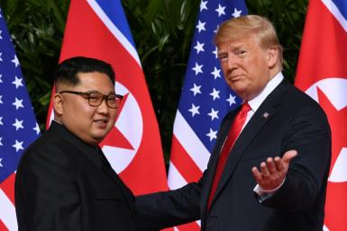 (FILES) In this file photo taken on June 12, 2018 US President Donald Trump (R) meets with North Korea's leader Kim Jong Un (L) on Sentosa Island in Singapore. The US has slapped sanctions on three North Korea government-sponsored hacking operations