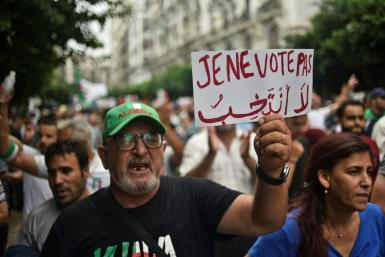 "An Algerian protester holds a placard reading ""I won't vote"" during a demonstration against the ruling class in the capital Algiers on September 13, 2019, for the 30th consecutive Friday since the movement began"