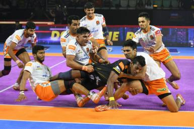 Siddharth Desai (centre) is grabbed by Puneri Paltan players in a Pro Kabaddi League match at the Thyagaraj Sports Complex in New Delhi