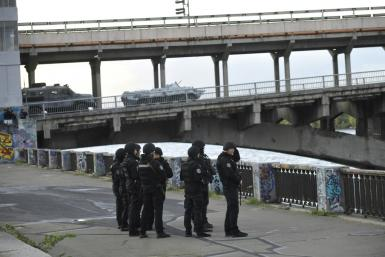 A large number of police cars and armed personnel carriers were at the scene, while special forces and snipers guarded the bridge after the man used his vehicle to block the bridge across the Dnipro river