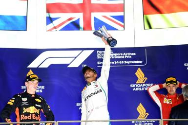 Lewis Hamilton celebrates his Singapore Grand Prix victory on the podium a year ago with second-placed Max Verstappen (left) and third-placed Sebastian Vettel