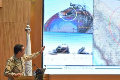 Saudi defence ministry spokesman Turki bin Saleh al-Malki shows off pictures as he alleges that strikes on the country's oil infrastructure came from the north and were 'unquestionably' sponsored by Iran