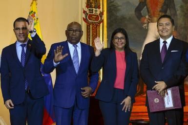 Venezuelan Foreign Minister Jorge Arreaza, Education Minister Aristobulo Isturiz, Vice President Delcy Rodriguez and opposition member Javier Bertucci pose after signing a dialogue agreement between the government and the opposition in Caracas