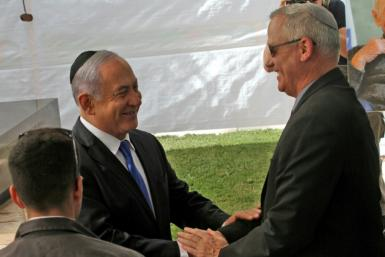 Israeli opposition leader Benny Gantz did not immediate respond to Netanyahu's call for a unity government but the two men exchanged greetings at a Jerusalem memorial service for Shimon Peres